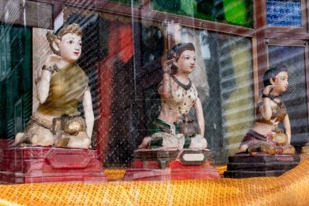 Old woman statue beckoning happy lot religious dolls in every Thai house for spirit or household divinity of Thailand called Nang Kwak. Thai doll for lucky in showcase glass.