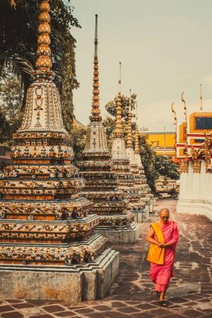BANGKOK,THAILAND-MAY 17,2017: Thai monk is walking in front of old ancient pagoda at Wat Pho Temple in Bangkok, Thailand.