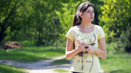 Girl running on forest path in a park and taking b...
