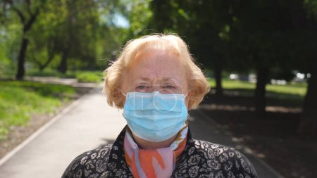 Photo for Portrait of old woman with medical face mask stands at city street. Grandmother wears protective mask from virus COVID-19 outdoor. Concept of health and safety life from coronavirus pandemic. Close up - Royalty Free Image