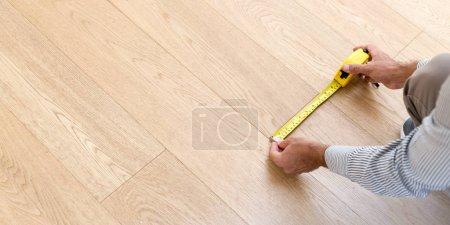 Photo pour Architecte prenant des mesures du nouveau plancher de bois franc. Accueil et concepts d'entretien - image libre de droit