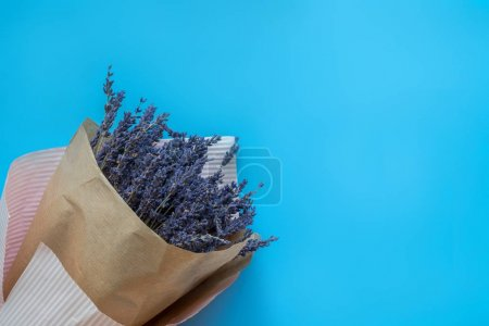 Photo for A bouquet of dry lavender in kraft paper on a blue background, symbolizing summer and France. Flat lay, top view - Royalty Free Image