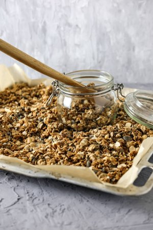 The process of storing homemade granola. A glass jar, a wooden spoon and a baking tray with a dry breakfast on the concrete background.