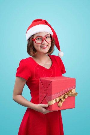 Photo pour Mme Santa. Belle jeune femme asiatique dans le chapeau du Père Noël tenant un cadeau isolé sur bleu . - image libre de droit