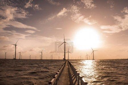Wind turbines against cloudy sky