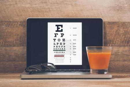 Laptop, eyeglasses and juice