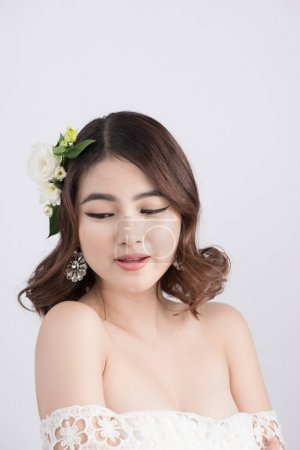 Beautiful asian bride with floral wreath on head s...