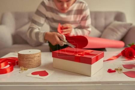 Man wrapping gifts in red ribbon and fresh roses. Valentines concept
