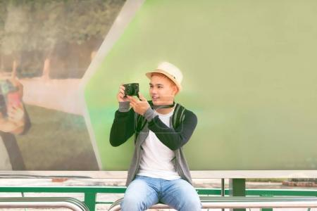 Young asian man in hat using smartphone taking photo of city