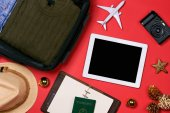 travel concept , passport, camera, hat, airplane, Christmas decorations on red background