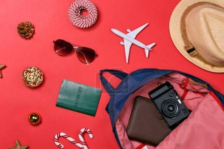 travel concept with passport, camera, hat, airplane, Christmas decorations on red background