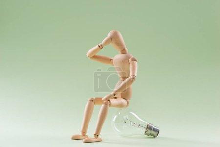 Photo pour J'en ai aucune idée. Mannequin en bois assis sur une ampoule incandescente - image libre de droit