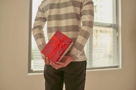 Man standing and holding red gift box behind his back