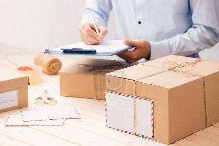 Courier making notes in delivery receipt among parcels at table