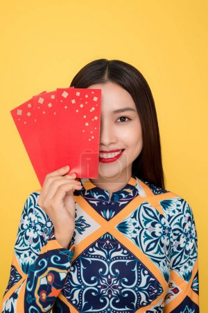 Vietnamese woman traditional festival costume Ao Da holding red money pockets. Tet holiday. Lunar New Year.