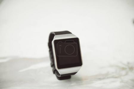 Unknown smart wrist watch laying on the table