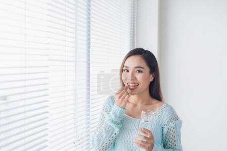 Young asian beauty young woman eating pills and drinking water
