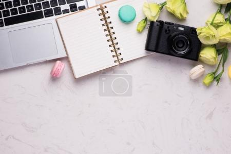 White desk with colorful macaroons, camera and laptop