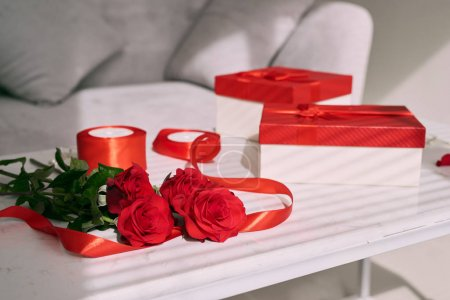 Greeting card for Valentines or Mother day. Gift box and red rose flower on table