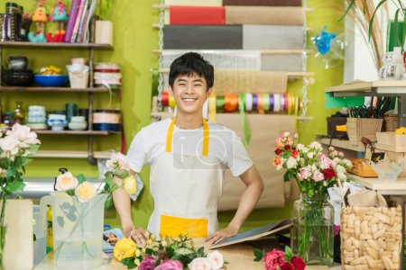 Portrait of smiling flower shop owner working. Small business.