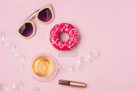 Delicate pink party background for celebrating accessories and donut.