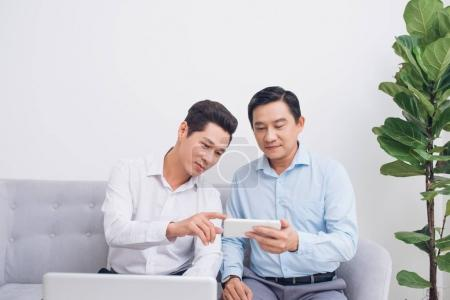 Portrait of two business partners sitting on couch at office usi