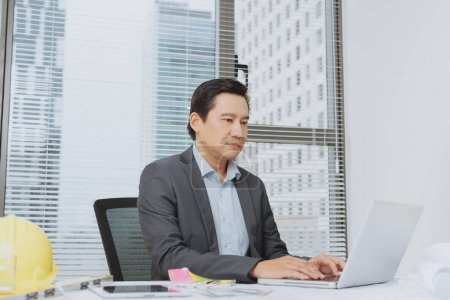 Professional construction manager working with blue print in office