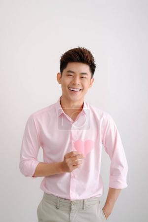 Handsome young asian man holding paper heart shaped valentine