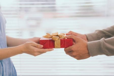 Couple in love. Romantic man giving gift to his girlfriend