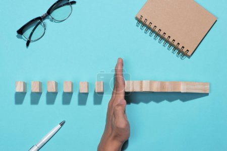 Hand of businessman stops dominoes continuous toppled