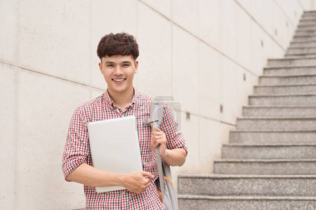 College asian male student holding laptop in campus