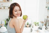 Happy young asian woman eating green apple. Dieting concept. Healthy food