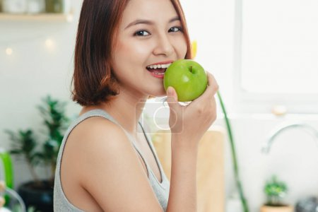 Beautiful asian woman eating green apple. Diet. Dieting concept. Healthy food