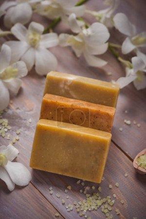Photo pour Morceau de savon naturel avec fleur sur une vieille table en bois - image libre de droit