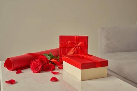 Valentine gift wrapping with rolls of  paper and bouquet of roses