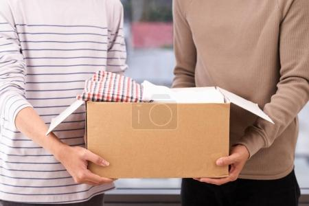 Man holding a clothes donate box. Donation concept.
