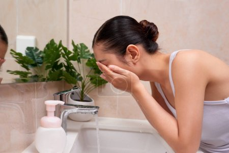 Asian young woman washing her face on the sink