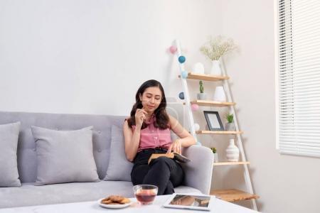 Photo pour Jeune belle femme asiatique assise sur le canapé lisant un livre profitant de son thé dans le salon à la maison - image libre de droit