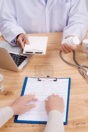 Stethoscope, medical prescription form are lying against the background of a doctor and patient discussing health exam results.