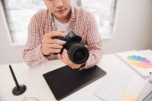 Male photographer sitting at his desk looking to camera