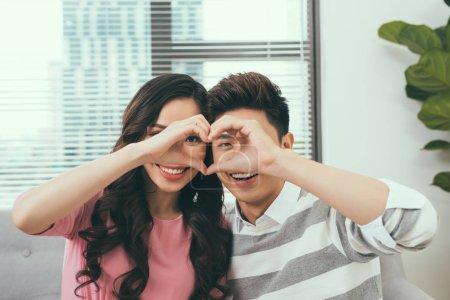 Séance de couple asiatique rapprochées et regardant à travers une forme de coeur avec leurs doigts