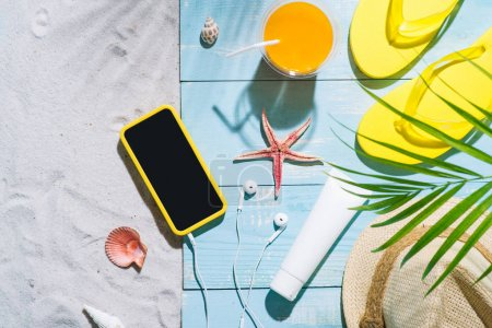 Summer holiday. Yellow flip flops, straw hat, orange juice and mobile phone