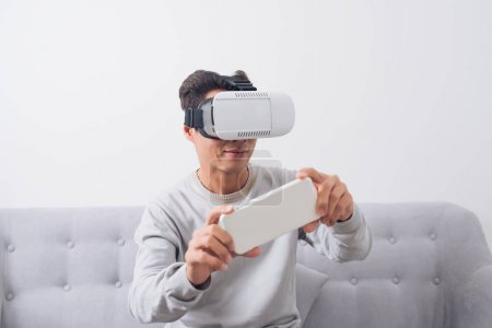 Asian man wearing virtual reality goggles