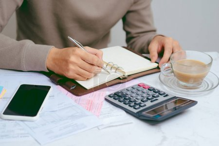 male hands doing finances and calculate about cost at home office.