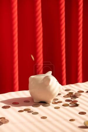 Coins falling into piggy bank. Money savings concept