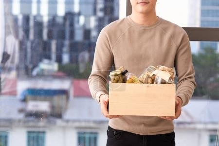 Volunteer with box of food for poor. Donation concept.
