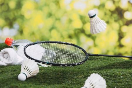 Shuttlecock and badminton racket with water and towel on the grass in the park.