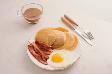 Photo for Breakfast plate with pancakes, eggs, bacon and fruit. - Royalty Free Image