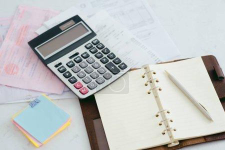 Foto de Pluma en papeleo con calculadora para Resumen ingresos o ganancias en el escritorio de oficina. - Imagen libre de derechos