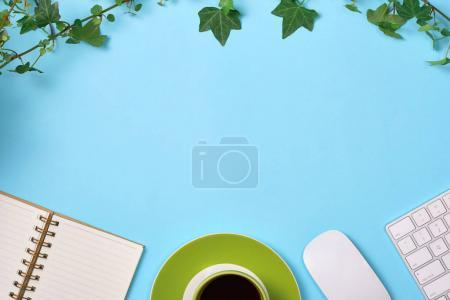 Photo for Top view of hot coffee in green cup with leaves, notepad, computer mouse and keyboard on blue background - Royalty Free Image